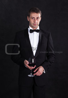 Stylish man in elegant black tuxedo with glass red wine