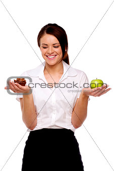 Business woman comparing fruit and chocolate