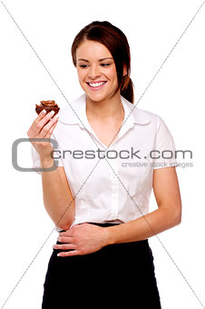 Business woman looking at a chocolate bun