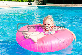 little girl with rubber ring in swimming pool