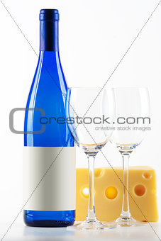 Blue bottle of white wine, two wine glasses and cheese