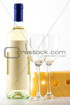 Bottle of white wine and two empty wine glasses and cheese