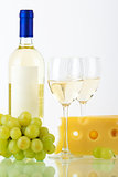 Bottle of white wine, wine glasses, cheese and grape