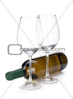 White wine bottle and two empty glasses