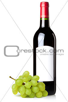 Red wine in bottle and grapes branch