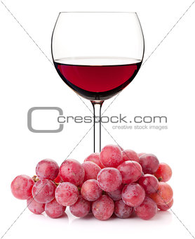 Red wine in glass with red grape branch