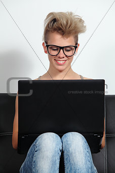 Fashion teenager girl sitting on a couch with a laptop and glasses