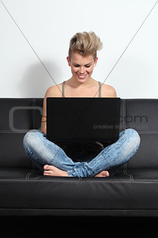 Fashion teenager girl sitting on a couch with a laptop