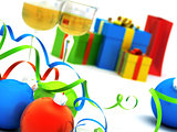 Christmas toys of different colours against glasses with champagne and gifts