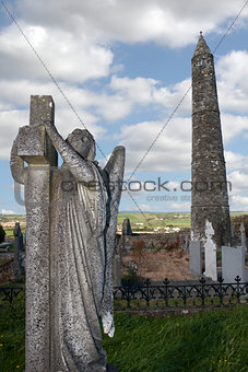 Archangel statue before an Ancient round tower