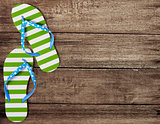 Green flip flop sandals on old wooden boards