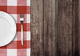 white plate and fork on old wooden table with red checked tablec