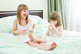 Two little girls drinking milk from glasses on bed