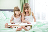 Two little girls reading book sitting on bed