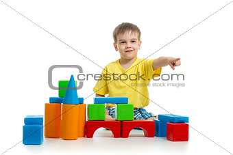 kid playing with colorful building blocks and pointing direction