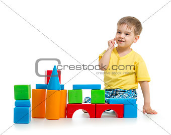 little boy is playing with colorful building blocks isolated on