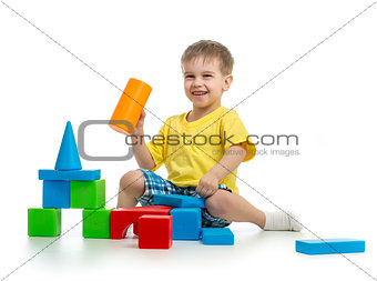happy kid playing with colorful building blocks on white backgro
