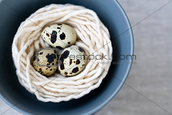 Three quail eggs in the nest with the thread on the plate