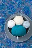 Bright balls of yarn and knitting needles on a plate