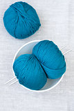 Three bright balls of yarn and knitting needles
