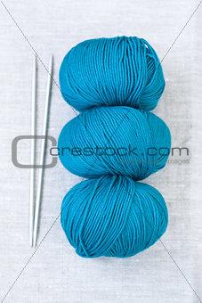 Three bright balls of yarn and knitting needles