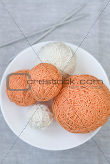Orange and white balls of yarn and knitting needles