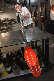 Man Blowing into Glass Object