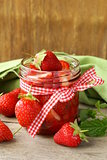 strawberry jam in a jar and fresh berries on the table