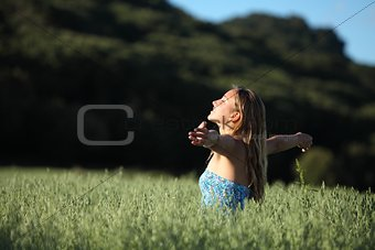 Beautiful woman breathing happy in a green meadow