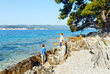 Summer stony beach and family on it (Croatia).
