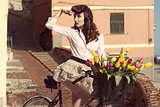 vintage pin-up with flowers on bike in old town