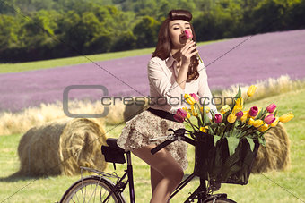 portrait of vintage pin-up on bike smelling a flower in rural co