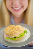 Closeup on plate with sandwich in hand of smiling teenager girl