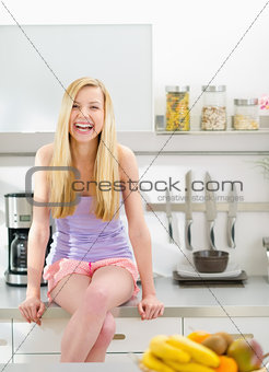 Portrait of smiling teenager girl sitting in modern kitchen