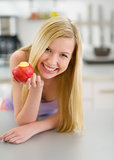 Happy teenager girl eating apple in kitchen