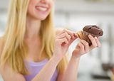 Closeup on chocolate muffin in hand of teenager girl