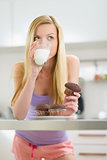 Teenager girl eating chocolate muffin with milk in kitchen