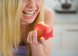Closeup on smiling teenager girl eating apple