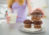 Closeup on teenager girl with milk taking chocolate muffin