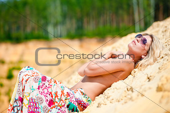The girl in sunglasses sunbathes