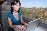 woman in a train computing laptop computer