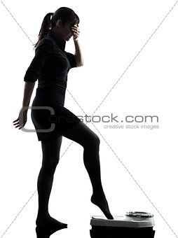 anxious woman standing on weight scale  silhouette