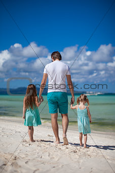 Father and his two kids enjoy walking by the sea