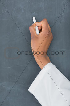 Close up of a teacher holding a white chalk