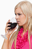 Serious blonde drinking a glass of wine