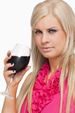 Serious blonde drinking a glass of red wine
