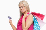 Smiling blonde holding shopping bags and credit card