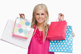 Smiling blonde showing shopping bags