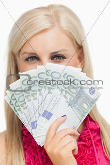 Beautiful blonde holding 100 euros banknotes