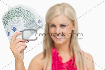 Beautiful blonde showing 100 euros banknotes